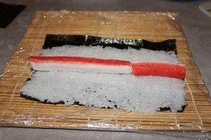 Выкладываю крабовые палочки на рис